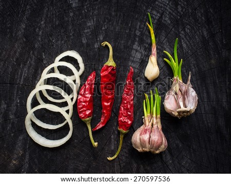 Onions, red pepper and garlic on a dark table - stock photo