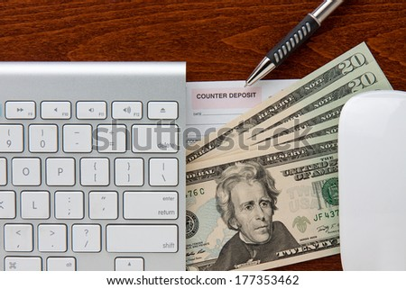 online banking. keyboard and mouse frame deposit slip and twenty dollar bills. pen points to deposit slip all are on top of a brown grain wood desktop