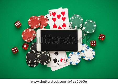 online casino concept, playing cards, dice chips and smartphone with copyspace on the green table. view from above. banner template layout mockup for online casinos and gambling.