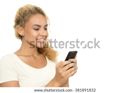 Online chat. Close up portrait of a young tanned girl with curvy dyed hair standing smiling and reading messages on her smartphone, isolated on white background