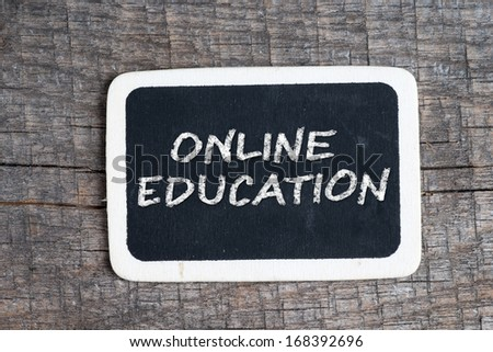 Online education handwritten with white chalk on a blackboard on wood background - stock photo