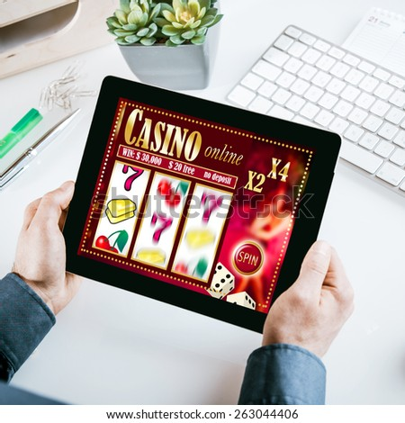 Online gambling concept with a businessman seated at his desk holding a tablet computer showing a casino interface with lucky numbers - stock photo