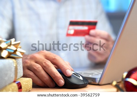 Online internet Christmas shopping concept with present computer mouse and hand - stock photo