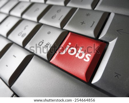 Online job search concept with jobs sign and symbol on a red laptop computer key for website and online business. - stock photo