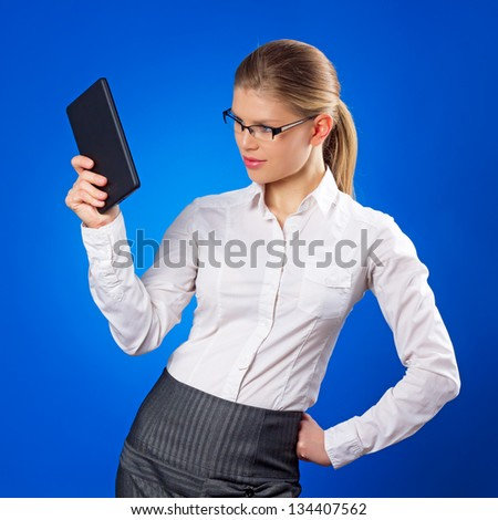 Online marketing. Sexy Caucasian business female in eyeglasses using tablet. - stock photo