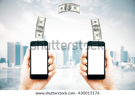 Online money transfer concept with two male hands holding smart phones with blank white screens and dollar bills above on city background. Mock up, 3D Rendering - stock photo