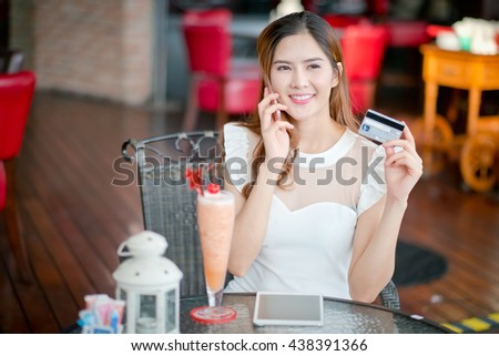 Online payment, Girl 's hands holding a credit card and using smart phone for online shopping - stock photo