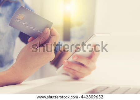 Online payment, hands holding a credit card and using smart phone for online shopping,credit card content,credit card background. - stock photo