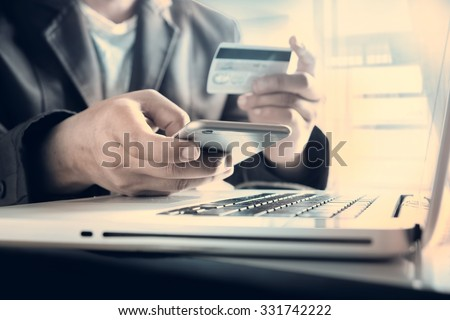 Online payment,Man's hands holding a credit card and using smart phone for online shopping  - stock photo