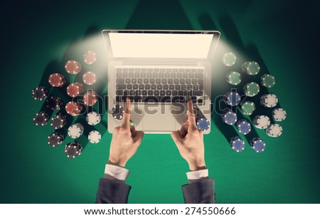 Online player's hands with laptop and stack of chips all around on green table top view, he is pointing to the computer screen - stock photo