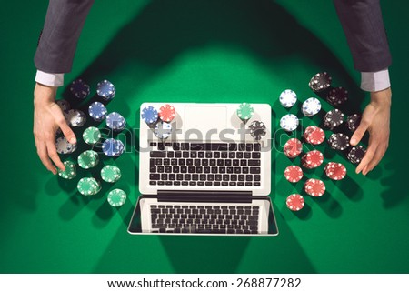 Online player's hands with laptop on green table top view, he is winning and taking all chips - stock photo