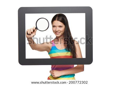 Online search concept. Bright happy young woman looking through magnifying glass, standing behind tablet frame. - stock photo