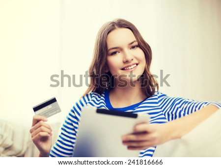online shopping and technology concept - smiling teenage girl with tablet pc computer and credit card - stock photo