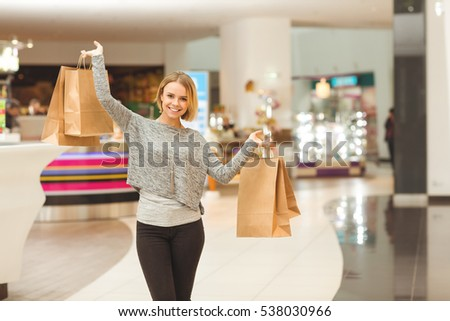 Online shopping. Beautiful young woman showing something on her smart phone to her handsome boyfriend while shopping together at the mall consumerism online shopping technology relationship concept