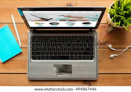 online shopping, business and technology concept - close up of laptop computer with internet shop web page on screen wooden table