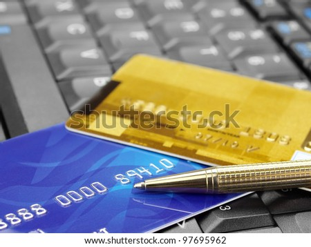 Online shopping. Closeup of credit cards and pen on computer keyboard - stock photo