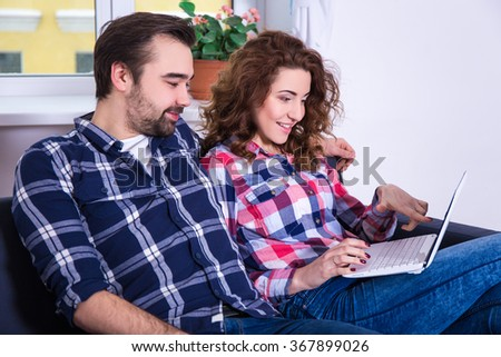 online shopping concept - cheerful couple searching something in internet on laptop at home - stock photo