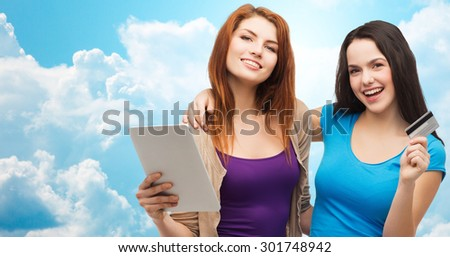 online shopping, e-money, commerce, people and technology concept - two smiling teenage girls or young women with tablet pc computer and credit card over blue sky with clouds background - stock photo