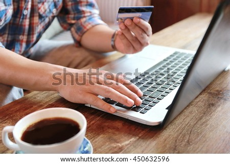 Online shopping,hands holding credit card and using laptop,personal loans, working on his laptop in coffee shop, businessman hand busy using laptop at office desk,shopping online lifestyle,credit card - stock photo