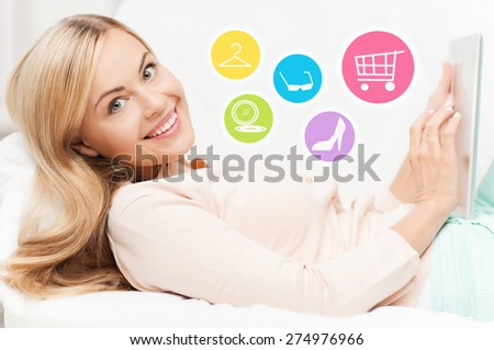 online shopping, sale, fashion and people concept - happy woman or housewife with laptop shopping online at home - stock photo
