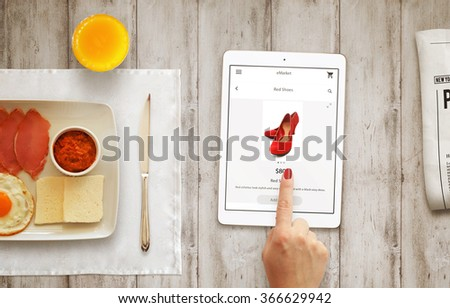 Online shopping with tablet with woman hand during breakfast.