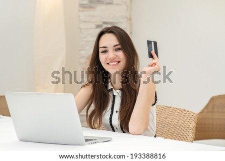 Online shopping. Young and pretty girl sitting at a laptop and making online purchases using credit and debit cards. Young girl smiling businessman in straight into the camera