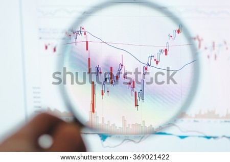 Online Stock Trading Platform with stock charts through a magnifying glass. Technical analysis. - stock photo