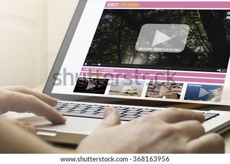 online streaming concept: man using a laptop with online streaming website on the screen. Screen graphics are made up. - stock photo