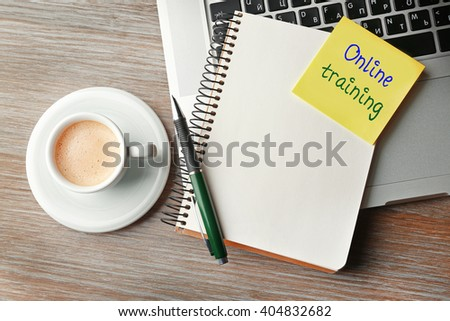 Online training written on sticky note, laptop, notebook and cup of coffee on table, top view - stock photo