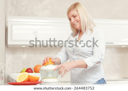 Only fresh and tasty juices. Smiling middle aged blond woman making orange juice in a juicer - stock photo