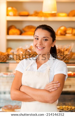 Only fresh pastry for our customers. Beautiful young woman in apron keeping arms crossed while standing in bakery shop - stock photo