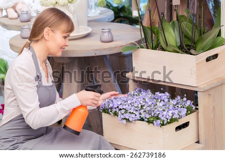 Only the freshest flowers. Young florist spraying water onto a floral arrangement at the wooden flower stand - stock photo