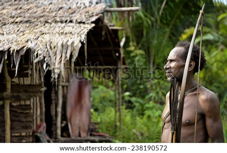 ONNI VILLAGE, NEW GUINEA, INDONESIA - JUNE 23: The Portrait Korowai man hunter with arrow and bow. Tribe of Korowai (Kombai , Kolufo).On June 23, 2012 in Onni Village, New Guinea, Indonesia  - stock photo