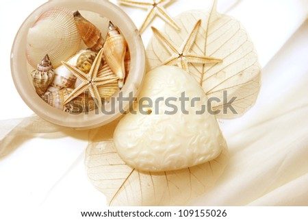 Onyx Bowl with shells, star fish, skeleton leaf and a heart shaped soap - stock photo