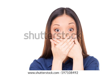Oops! Surprised young Asian woman covering mouth with hands and staring at camera while standing isolated on white - stock photo