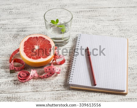 Open a blank Notepad, a grapefruit, a glass of water and measuring tape on a light wooden table. The concept of a healthy lifestyle, healthy food, diet - stock photo