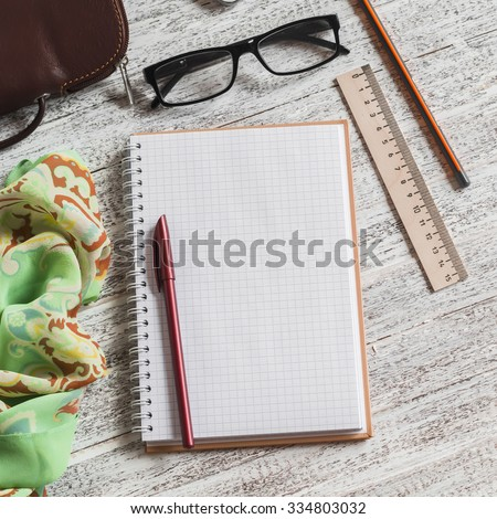 Open a blank Notepad, pen, glasses, handbag and scarf on white wooden table - stock photo