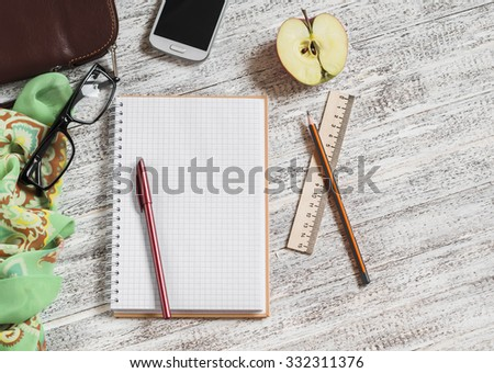 Open a blank Notepad, pen, glasses, phone, handbag and scarf on white wooden table - stock photo