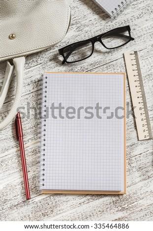 Open a blank white notebook, pen, women's bag, ruler, pencil  on the white desk - stock photo