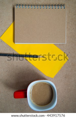 Open a blank white notebook, pencil cups of coffee on the table. - stock photo