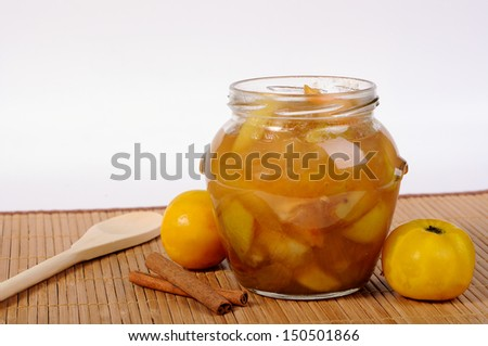 Open a jar with apple jam, yellow apples and cinnamon - stock photo