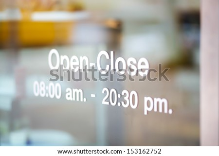 Open and Closed Sign on glass door - stock photo