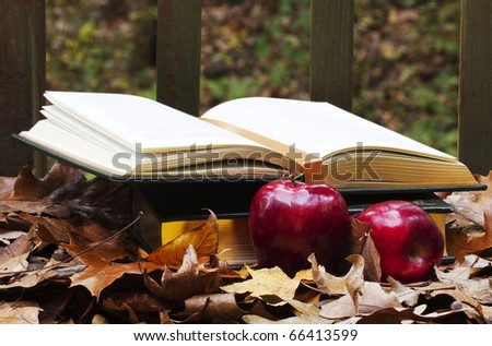 Open and closed textbooks nestled in colorful autumn leaves with red, fall harvest apples in foreground depict academics, homework, and study needs deep into the fall semester - stock photo