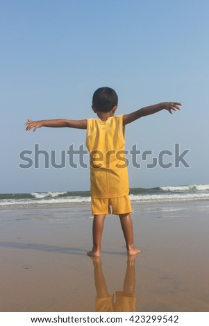 Open arms. Child express her freedom at sea beach. She is enjoying life. - stock photo