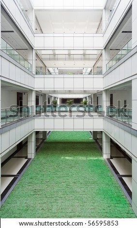 Open atrium with  facing corridors and man made lawn floor in an office building - stock photo