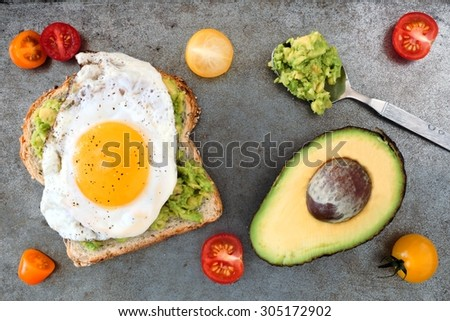 Open avocado, egg sandwich on whole grain bread with cherry tomatoes ...
