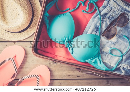 Open bag with beach or summer clothes - stock photo
