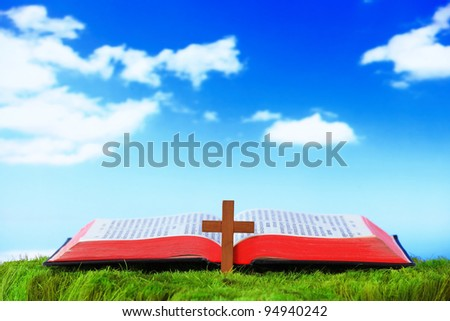 Open Bible and cross On The Grass with sky background - stock photo
