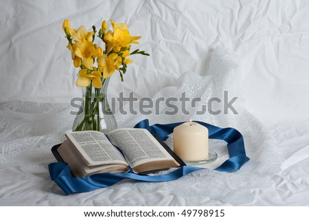 Open Bible and flowers candle and ribbon - stock photo