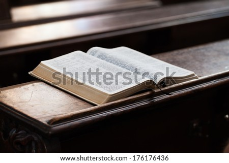 Open Bible on a church bench - stock photo